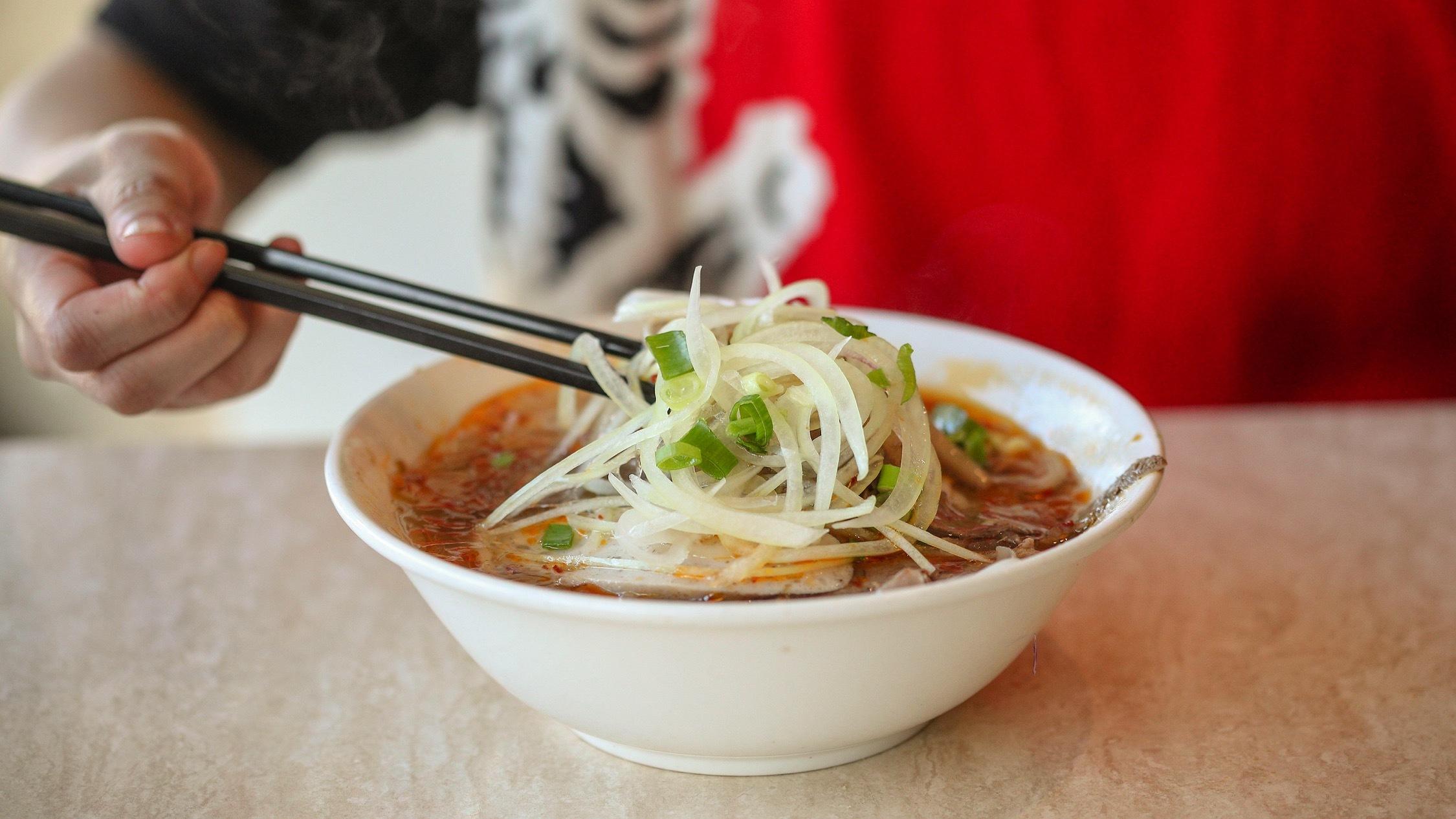 Person eating noodles at Dong Ba