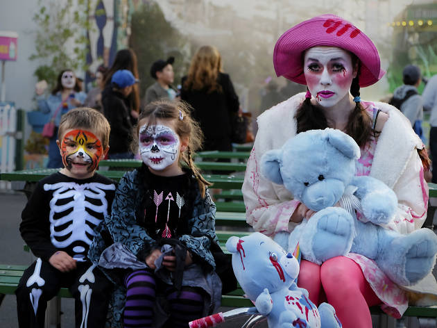 Two children and a woman dressed in Halloween costumes