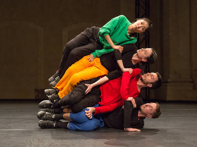 Four performers stacked on top of each other on stage