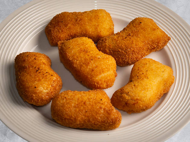 Six golden, succulent chicken nuggets on a white plate