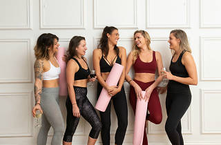 Five women wearing yoga clothes and holding glasses of wine