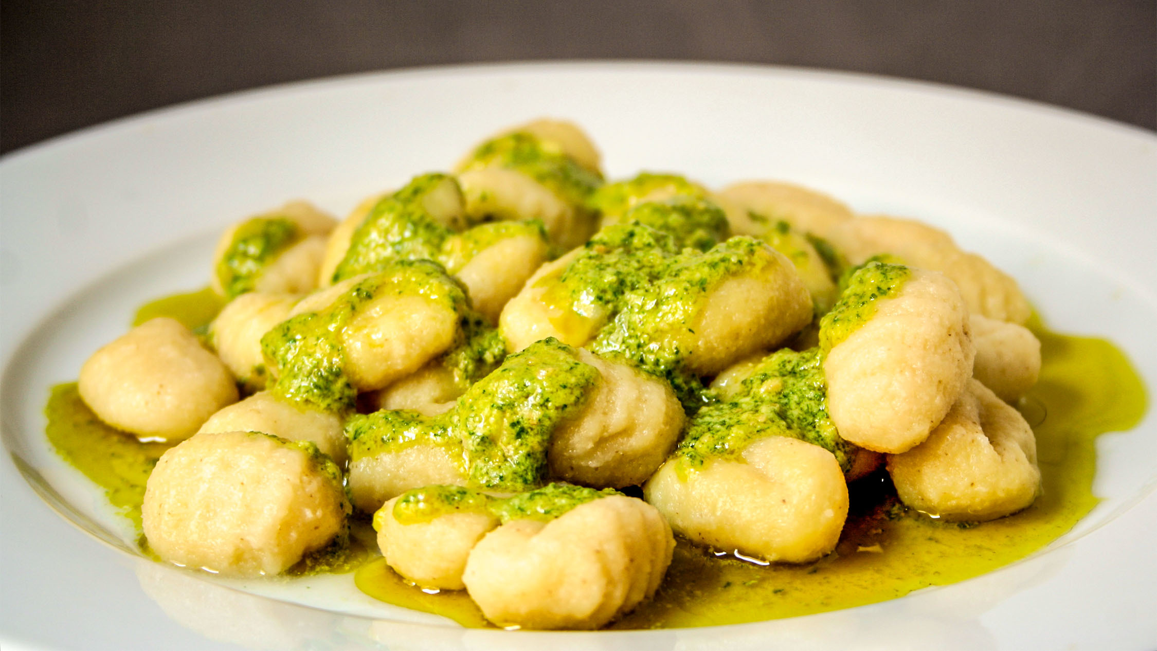 A plate of gnocchi with pesto