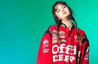 A press shot of pop artist Mallrat wearing a red jumper.