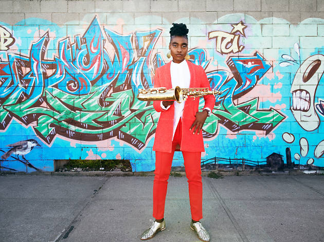 US jazz saxophonist Lakecia Benjamin holding a saxophone, standing in front of a gratified wall.