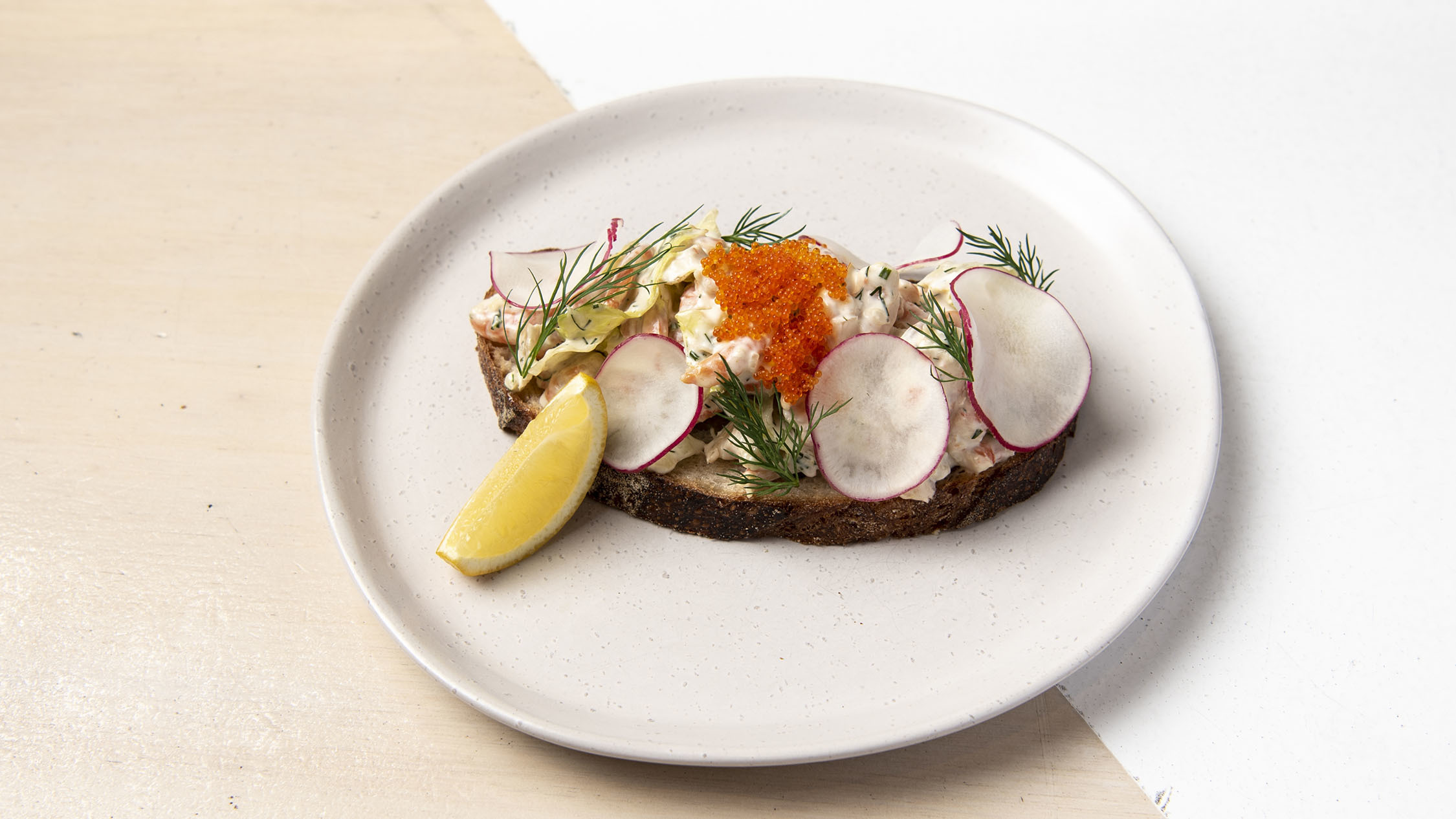 A piece of toast on a plate with prawn salad on top