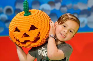 Child holding a jack-o-lantern made out of Lego