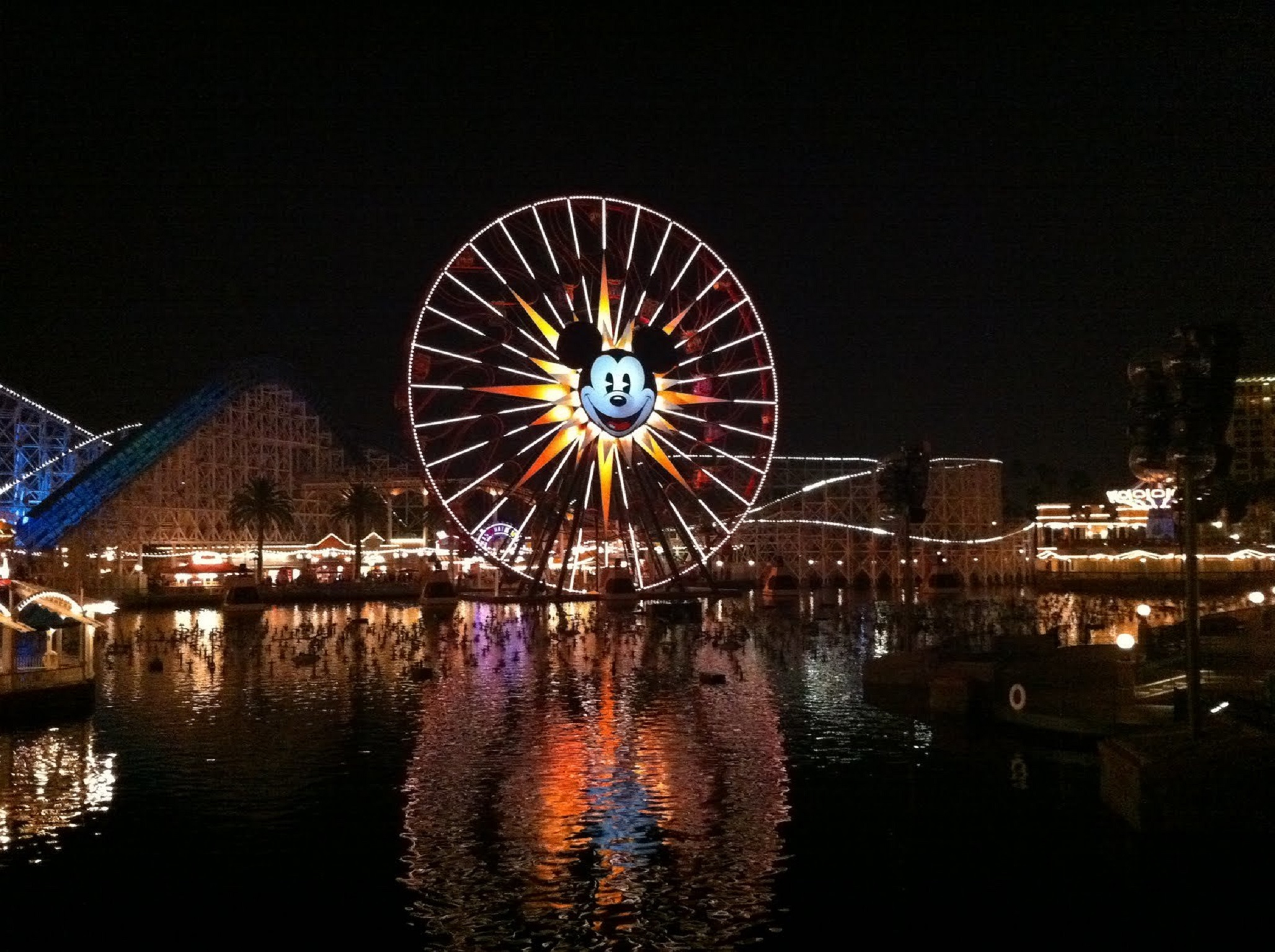 A ferris wheel with Mickey's face on it lit up in the dark