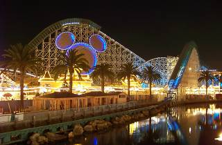 A rollercoaster with mouse ears on it at night
