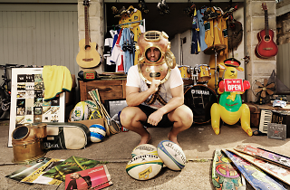 Man surrounded by garage sale goods
