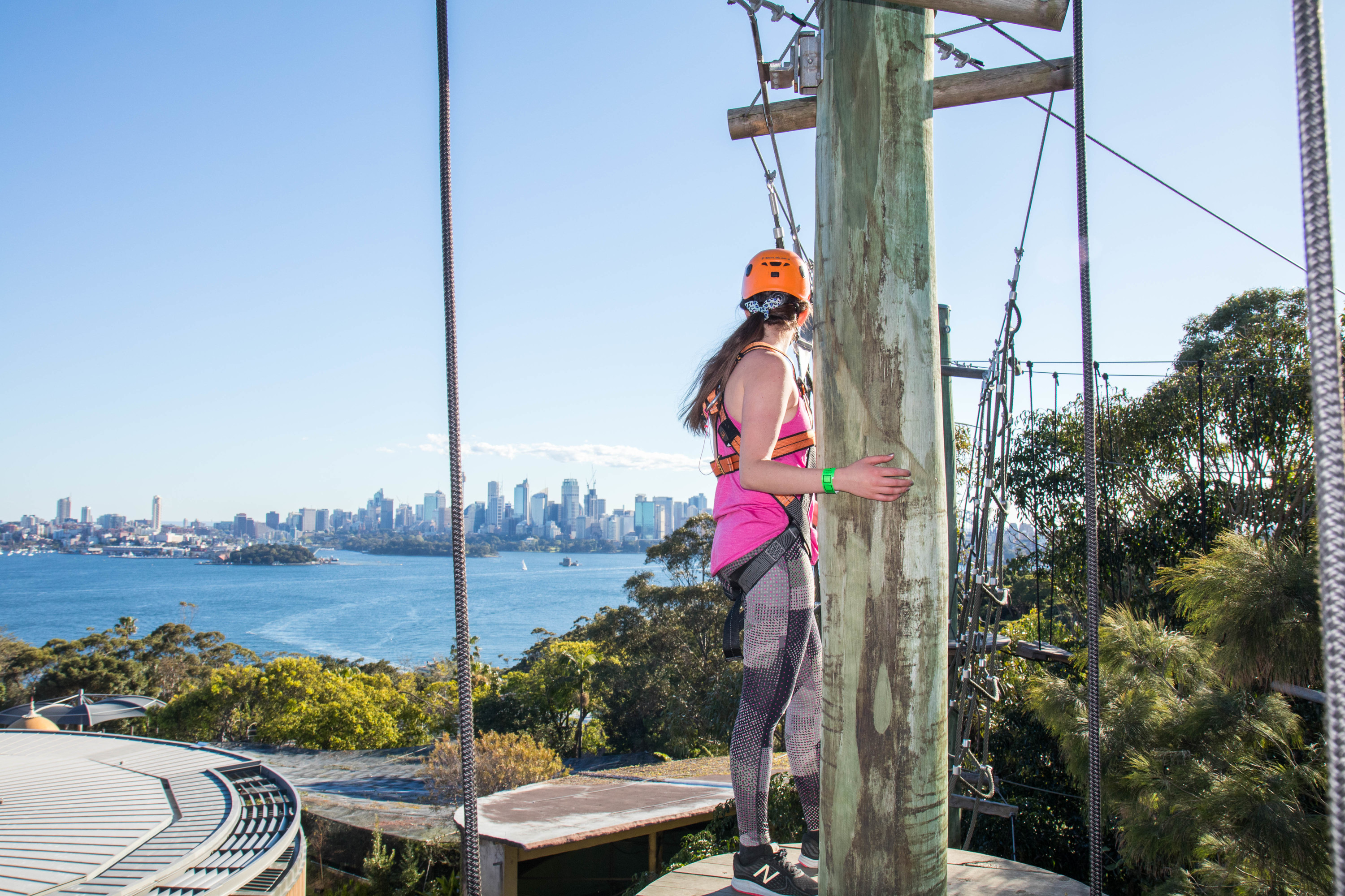 Girl standing on platform mid high ropes course at Taronga Zoo, looking at the view of the harbour