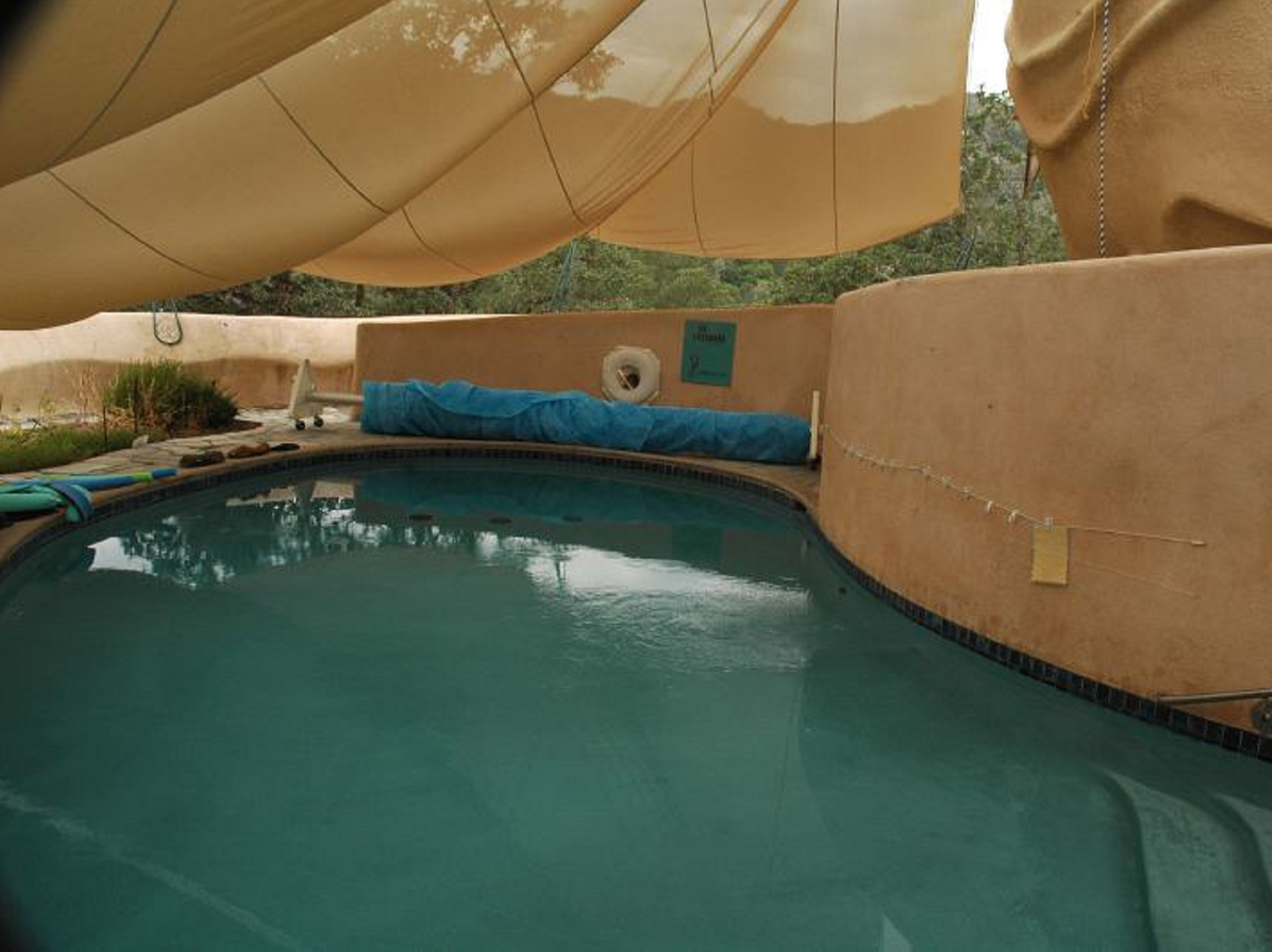 A pool with a tan tent over it