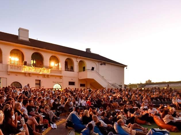 People sitting at the Bondi Pavillion for outdoor screenings at Flickerfest.
