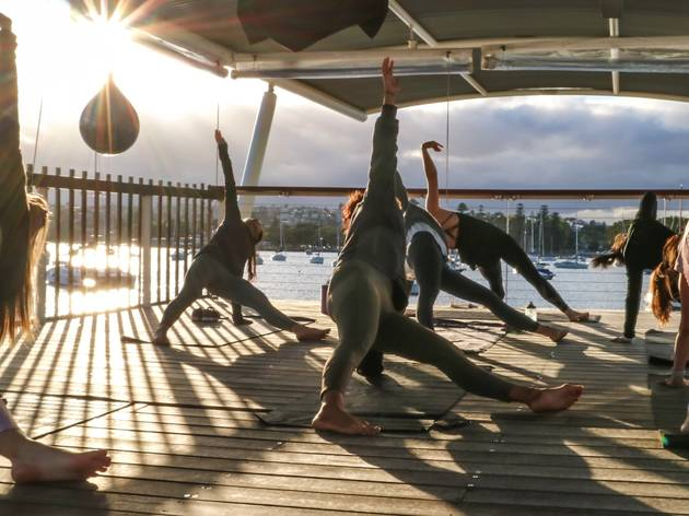 People doing yoga stretches on wooden deck at Sydney Harbour Yog