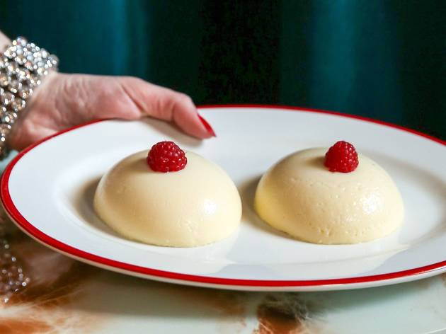 A hand with red painted nails and a diamond cuff holds out a plate with two panna cotta sitting side by side with raspberries on top