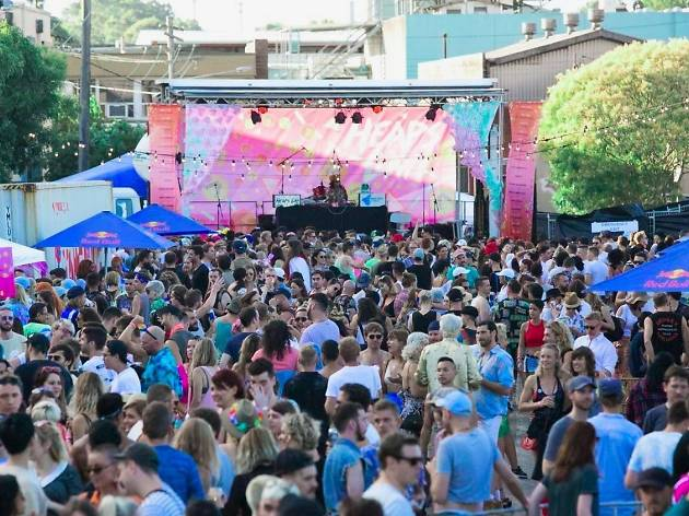A festival crowd assembled in front of a stag with a large pink back-drop emblazoned with the 'Heaps Gay' logo