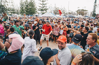 A crowd gathers at an outdoor festival, a man in a red t-shirt dances in a red tshirt, people are smiling, in the distance an Elmo toy bobs along on atop a stick.