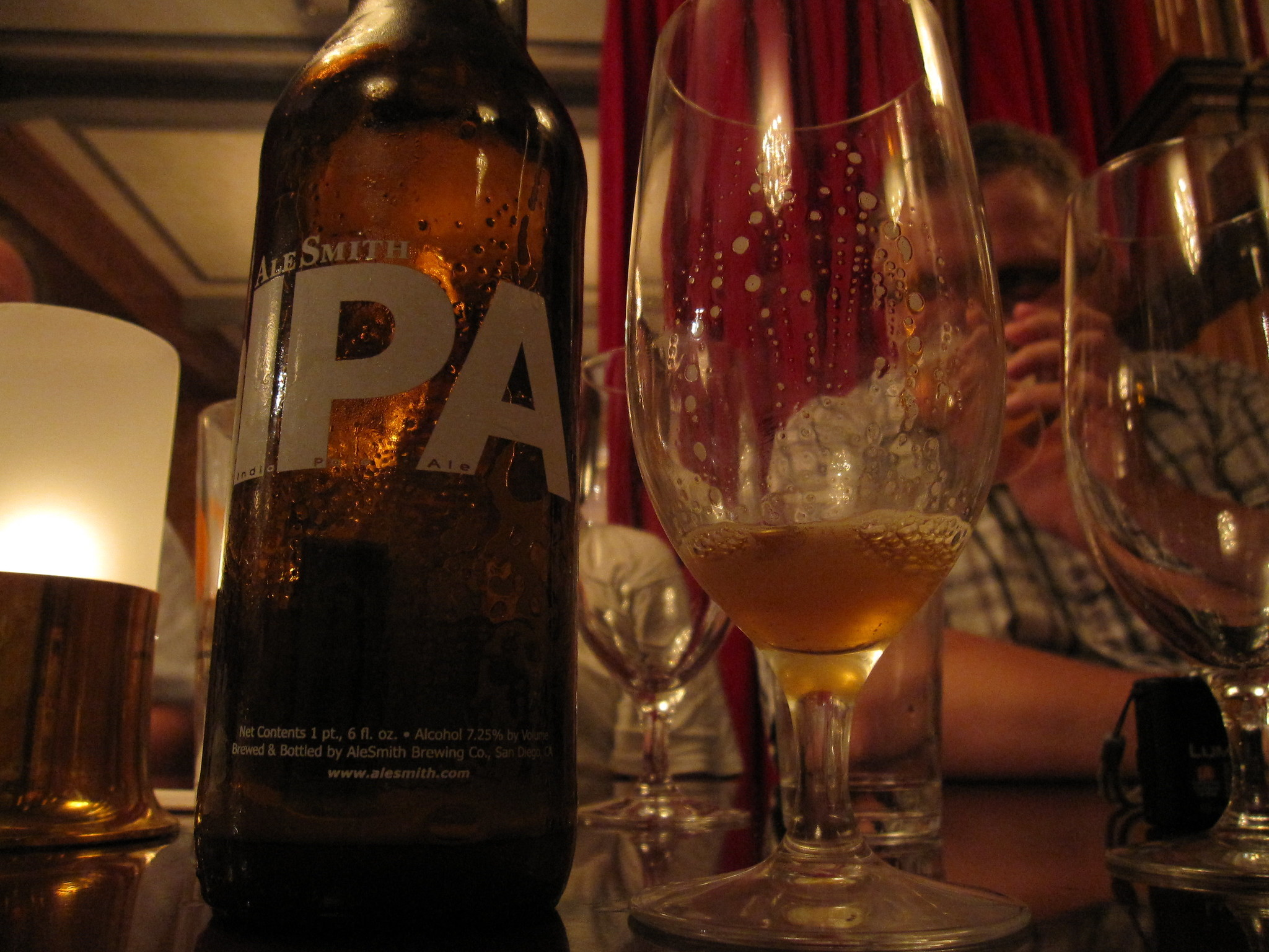 A bottle of beer and empty glasses with a man drinking a pint behind