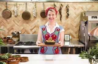 Rachel Jelley standing in an open kitchen holding a plate