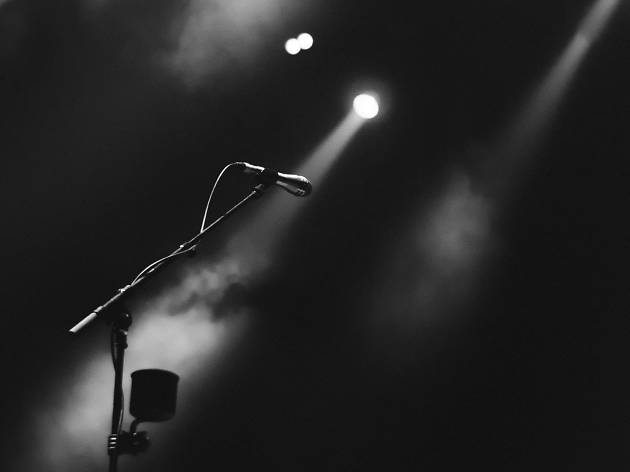A lone microphone stand stands on an empty, foggy stage with a spotlight on it.