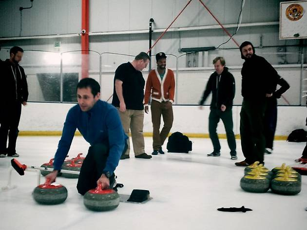 Several men on the ice, one kneeling with curling equipment