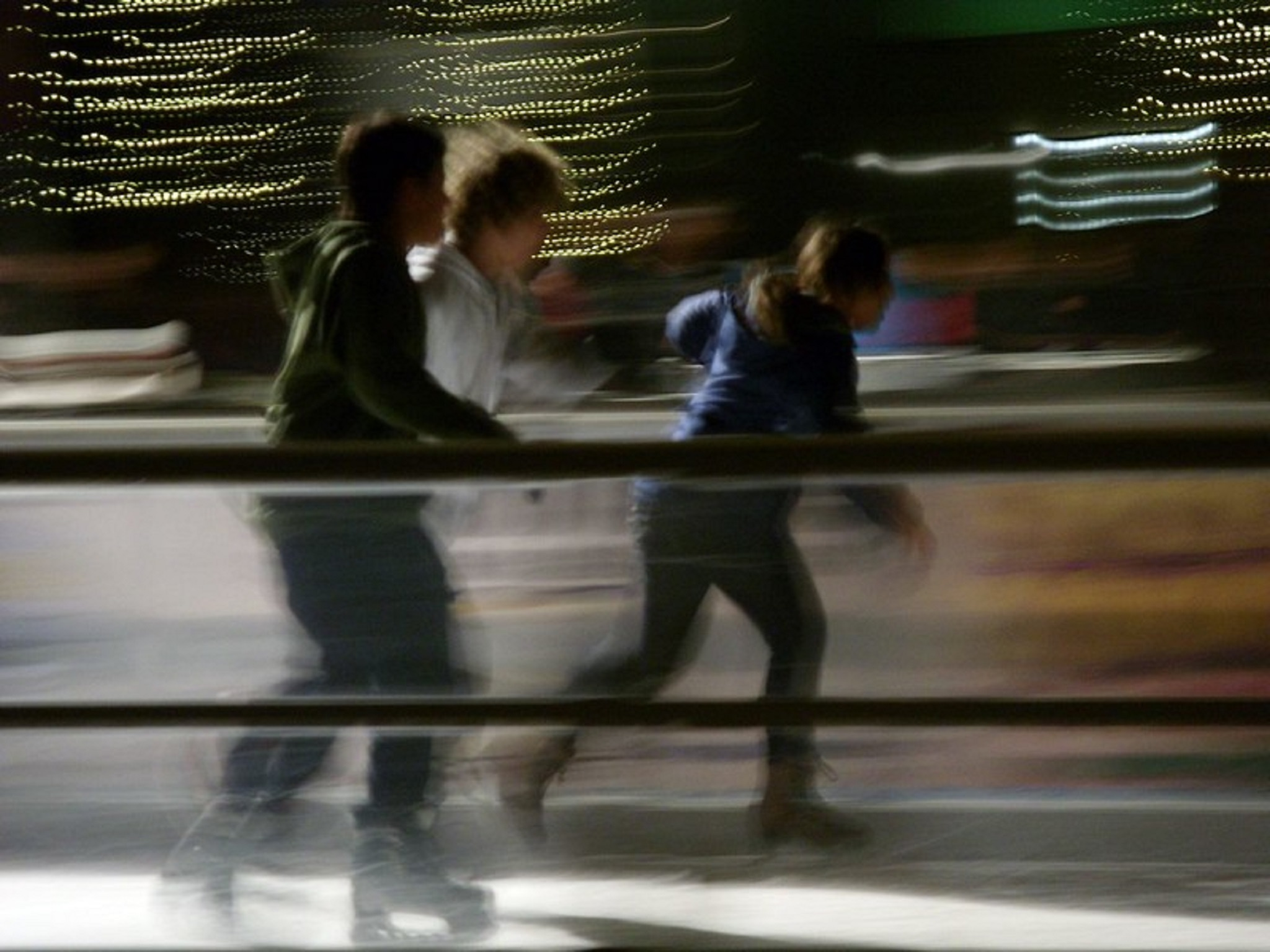 Three kids skating on an ice rink with blurred lights behind them
