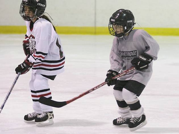 Two kids in helmets and uniforms playing ice hockey