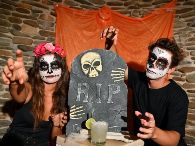 Two people in skull makeup leer at the camera, a headstone and a cocktail sit between them.