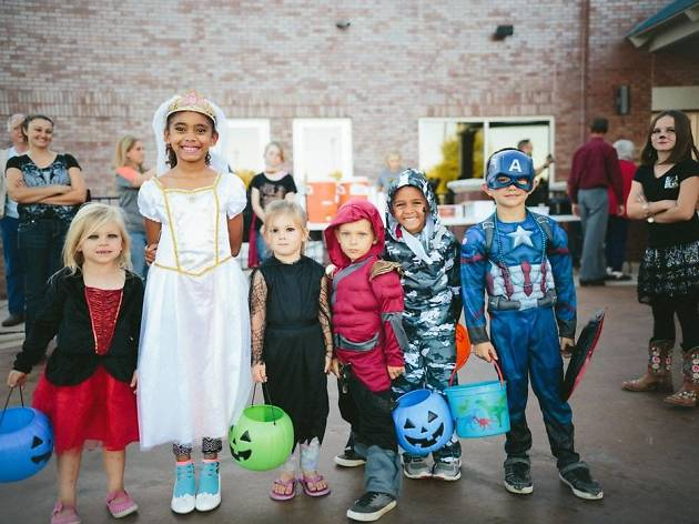 A row of children in halloween costumes smile at the camera, they are holding plastic pumpkins full of treats.