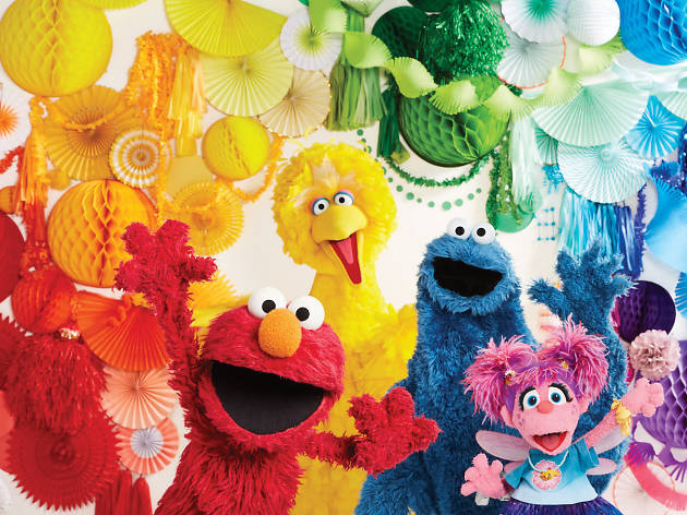 Sesame Street characters in front of colourful decorations