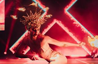 A woman dances with fire wearing a large gold headdress with fire on it, she is on a dark red-lit stage with a large 'X' made of fire behind her.