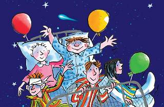 An illustration of a group of children in pyjamas riding though the night sky on a hospital bed with colourful balloons tied to it.