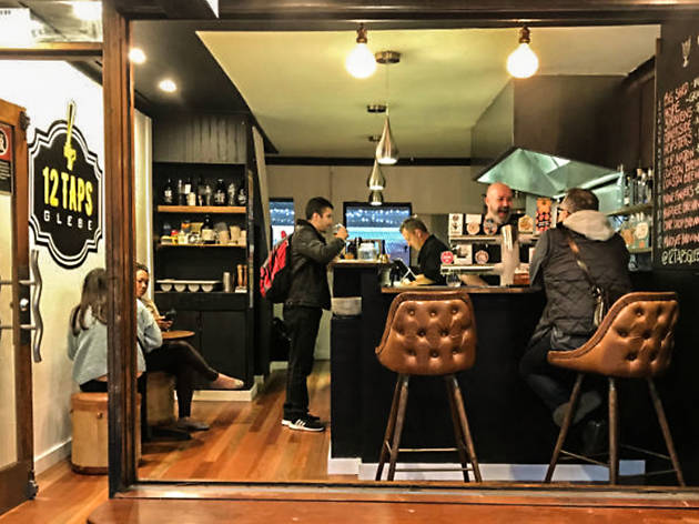 A few people gathered inside 12 Taps beer bar in Glebe