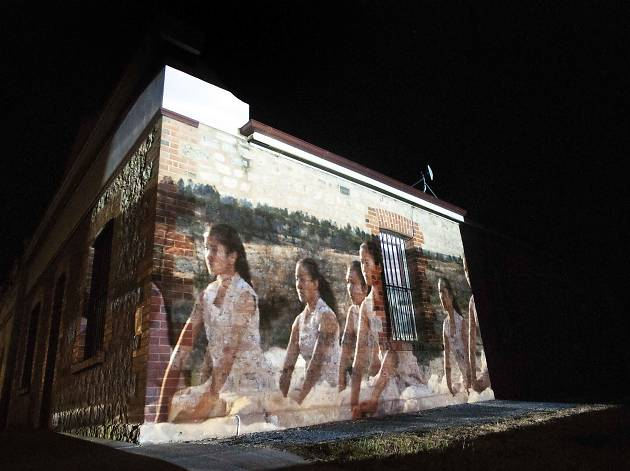 An image is projected on a brick structure, depicting a group of young women dancing in white dresses in an arid landscape.