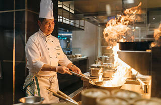 A chef frying noodles in a flaming wok