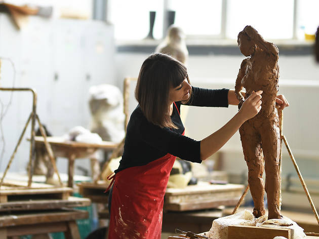 Woman in studio shaping a clay sculpture of a woman
