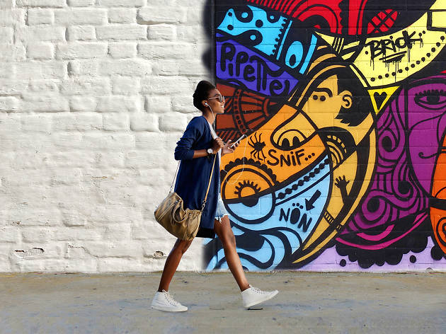 Woman walking past a wall covered in graffiti
