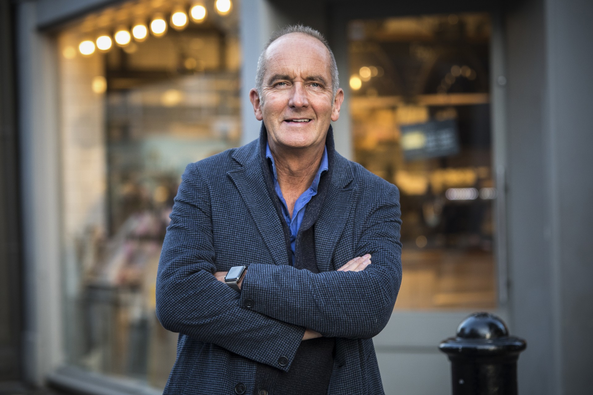 Grand Designs host Kevin McCloud stands wearing a jacket.