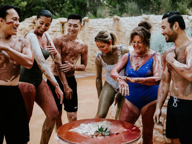 Group of people painting themselves with different clays