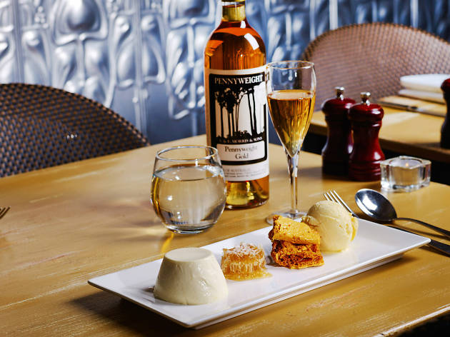 A table with a plate of ice cream, honeycomb and wine on it