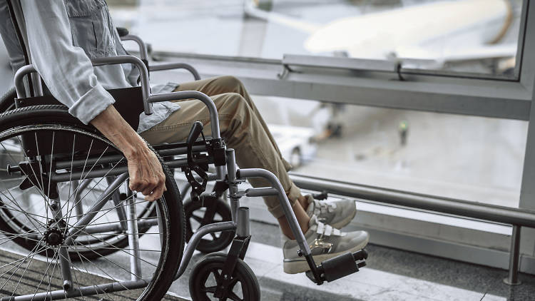 Old woman on wheelchair near window in airport