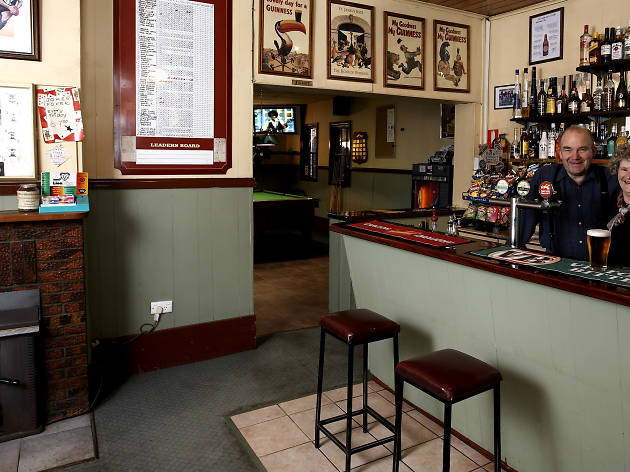 Man and a woman standing behind a bar in a pub