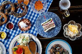 A gingham covered table topped with pretzels, beers, schnitzels and sandwiches