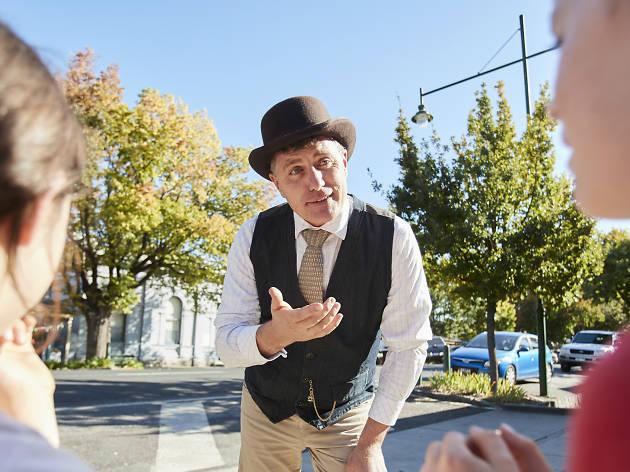 Man wearing bowler hat explaining something to two children
