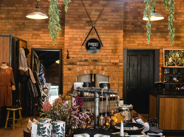 A brick-walled shop with plants hanging from the ceiling and a long table in the middle of the room covered in merchandise
