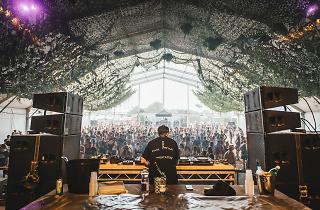DJ on stage with big crowd.