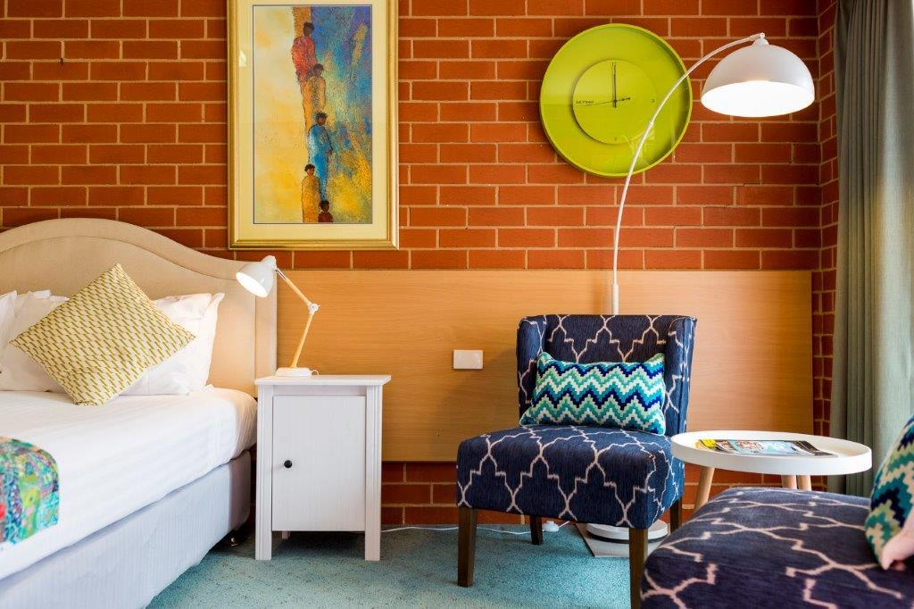 A room featuring a bed, bedside table, two colourful armchairs, a modern lamp and artwork