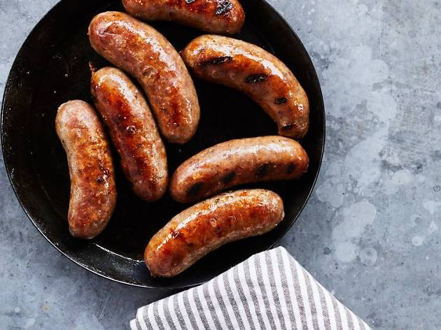 A pan of thick juicy sausages on a grey bench with a striped tea towel wrapped around the handle.