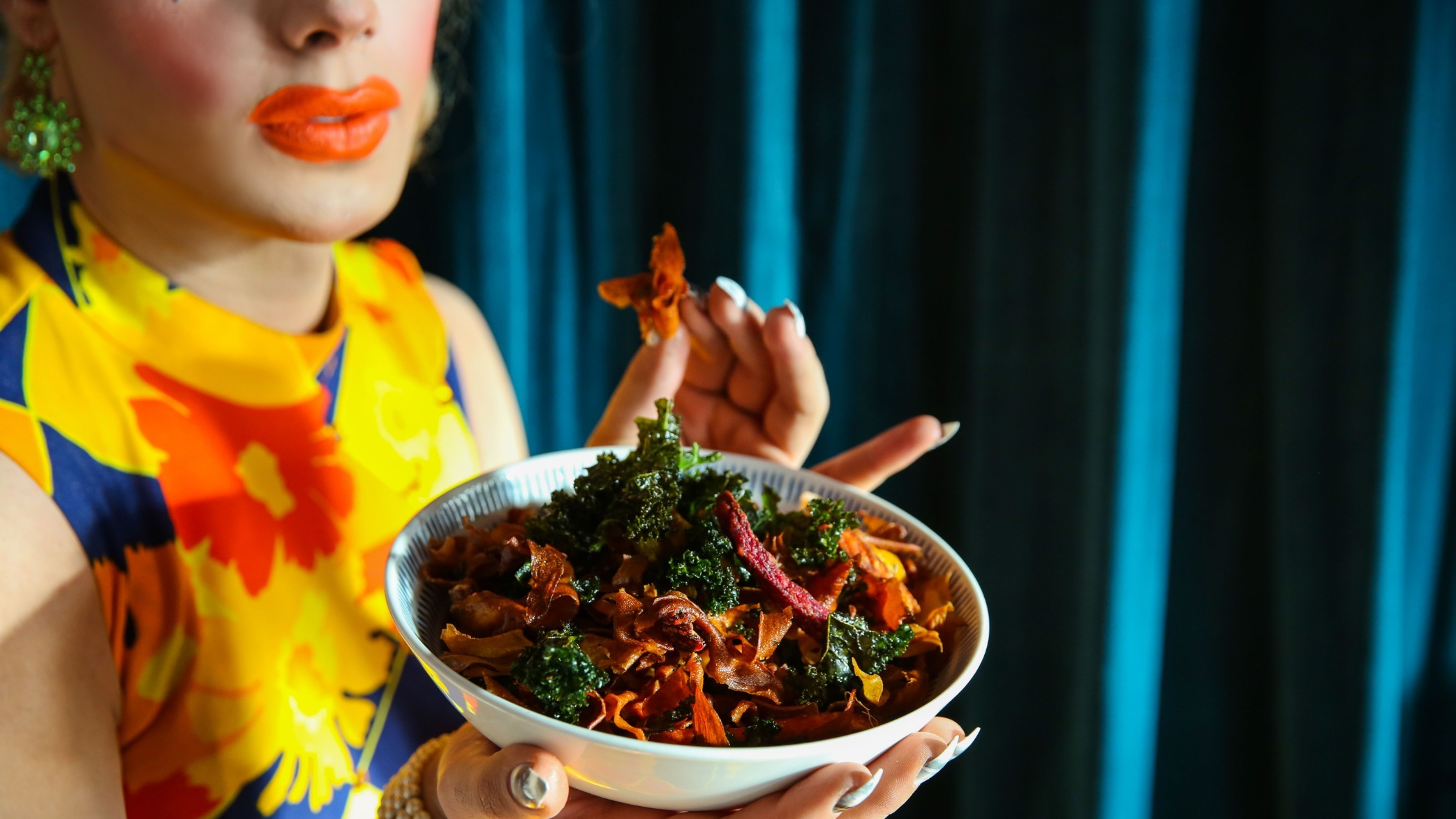 A person with bright makeup, orange lipstick and a floral dress holds up a salad full of sweet potato crisps.