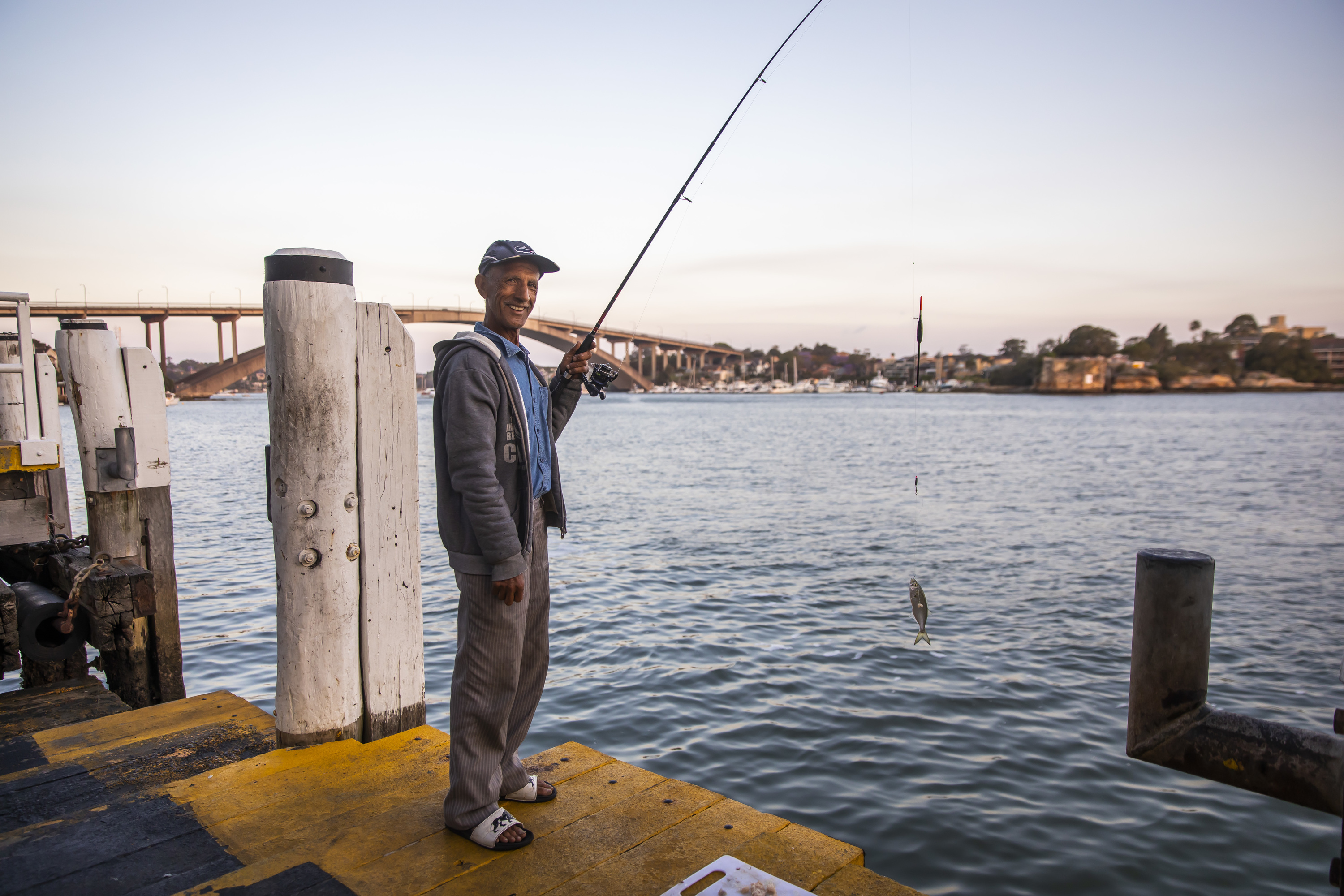 Man holding a fishing rod with fish hooked at Huntleys Point Wharf in Gladesville.