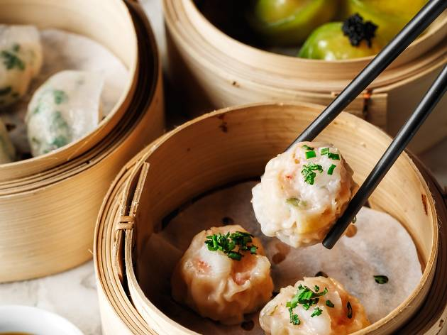 A hand holding a set of chopsticks lifts a dumpling from a steaming basket of dumplings.